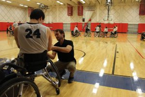 scott with man in wheel chair in basketball court