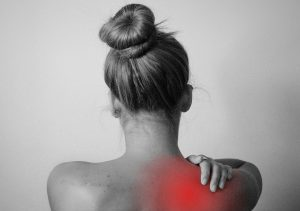 Woman holding shoulder, pain radiating shown in red.